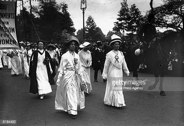Emmeline Pankhurst leads a suffragette parade through London with the protesters all dressed in white Accompanying them is a mounted policeman