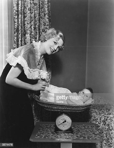 British character actress Enid StampTaylor weighing her baby daughter Robin Anne in a set of scales at home at Maida Vale London