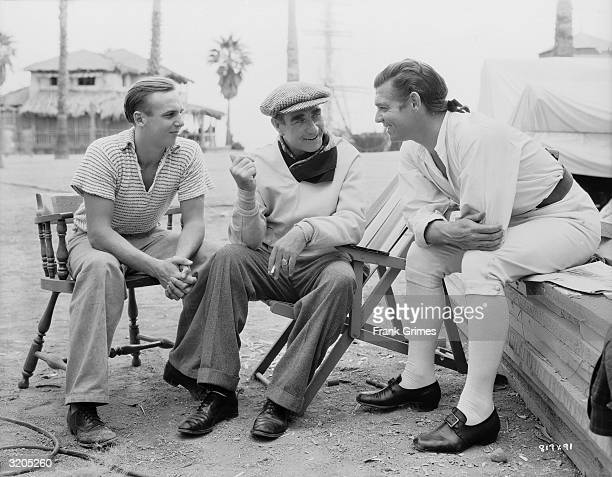 American actor Clark Gable converses with director Frank Lloyd on the set of 'Mutiny on the Bounty'