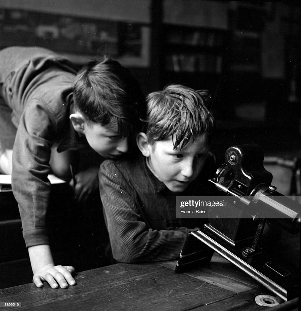Two boys examining the film projector that their class uses, looking inside to see how it works. Original Publication: Picture Post - 4564 - The Magic Lantern Grows Up - pub. 1948