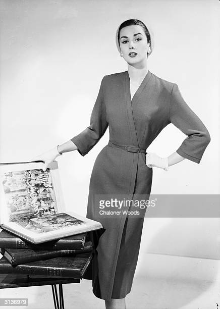 A woman in a Brilkie wraparound dress and tightfitting cap opens the pages of a bound copy of The Graphic