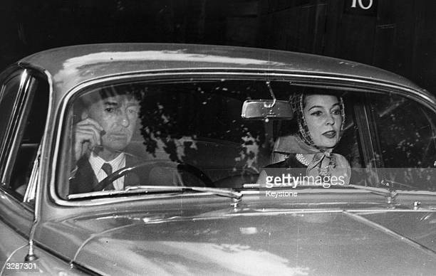 John Profumo ex War Minister and his wife Valerie Hobson in their car a fortnight after his statement in the House of Commons that he had lied about...