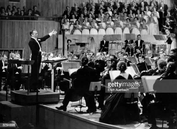 British conductor Sir Malcolm Sargent conducting the Sydney Symphony Orchestra and the Royal Choral Society at the Commonwealth Festival, Royal...
