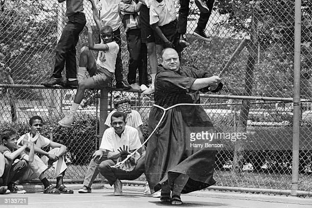 Friar Capistran Ferrito plays baseball with boys from Harlem New York City