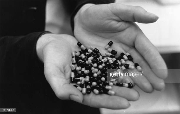 A closeup of hundreds of drug capsules held in a pair of hands