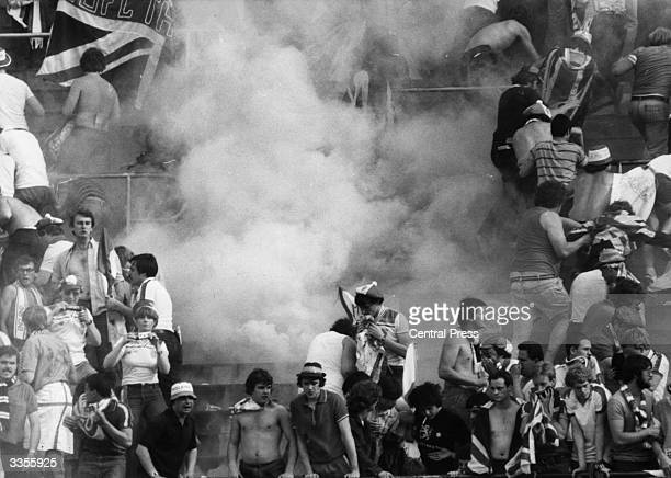 English and rival football fans fighting on the terraces at Turin during a European Nations Cup match. The 'smoke' surrounding them is tear gas...
