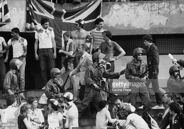 On the terraces, English and rival fans being controlled by Italian police during a European Nations Cup match against Belgium which was played in...