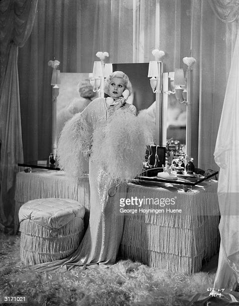 Dressed in a white lurex evening gown, Jean Harlow makes a telephone call from her luxurious bedroom in a scene from the fim 'Dinner at Eight',...