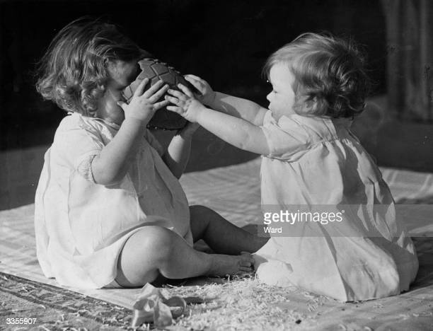 Two baby girls enjoying a chocolate Easter egg