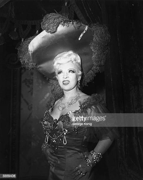 American actress and Vaudeville star Mae West wearing an outlandish hat in London.