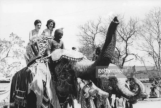 First Lady Jacqueline Kennedy and her sister, Lee Radziwill, riding an elephant in Jaipur, India.