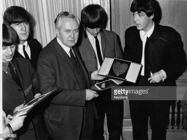 The Beatles from left to right Ringo Starr John Lennon George Harrison and Paul McCartney receive Variety Club awards from Labour MP Harold Wilson...