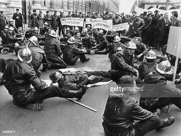 French firemen gather in Paris to stage a sitdown protest in the Rue de Rivoli during a demonstration for improved workinf conditions