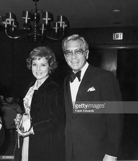 American actor Betty White stands smiling with her husband TV producer and host Allen Ludden wearing a tuxedo at an International Broadcasting Awards...