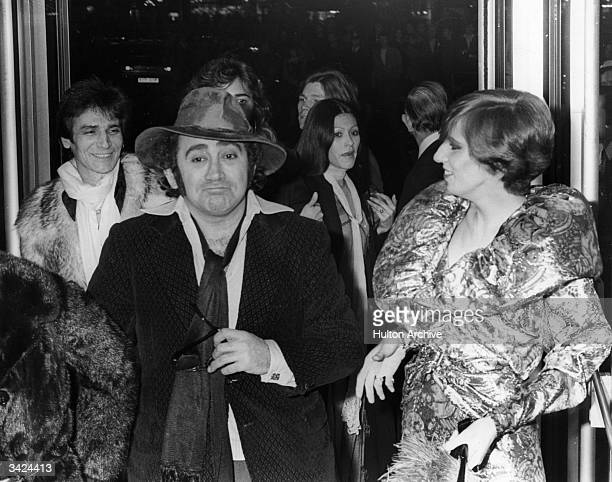 The English composer, lyricist and dramatist Lionel Bart clowns, to the amusement of Angie Bowie, wife of singer David Bowie, at the premiere of...