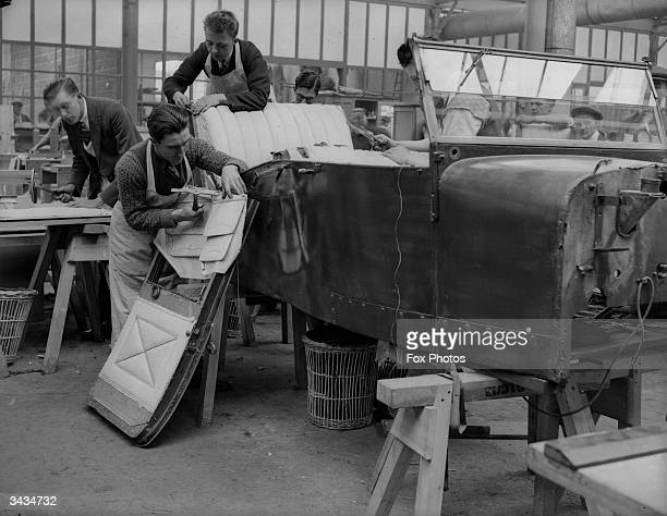 A car chassis stands on a trestle as unemployed miners learn a new trade in a car upholstery workshop on a government training estate at Stafford Rd...