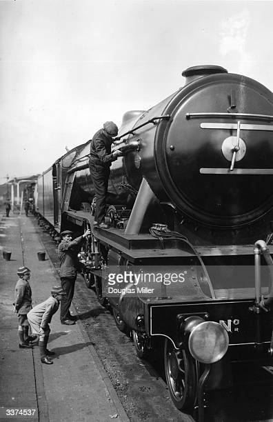 Two boys watch a couple of workmen polish the Flying Scotsman engine at Southend