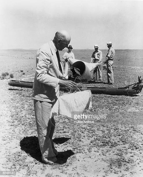 American physicist Dr Robert H Goddard inspects the cap and pilot parachute of a rocket after a successful launch in a field in Roswell New Mexico