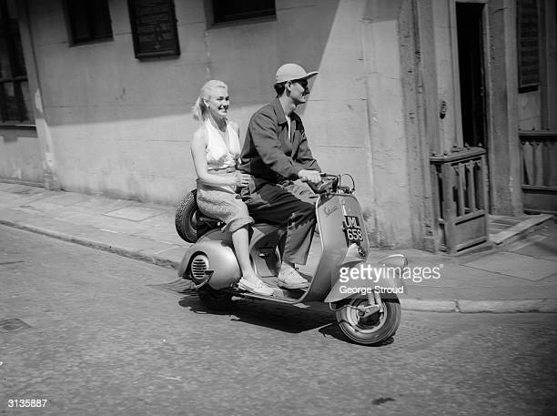 Actor and former acrobat Bonar Colleano and English actress Susan Shaw on a Vespa scooter