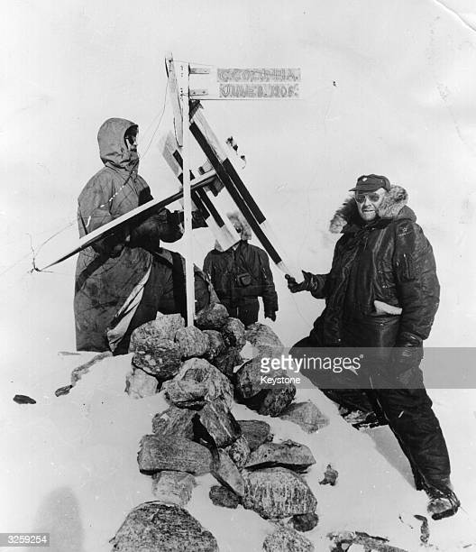 Lt Col Fletcher left and Lt Col Bennedict of the US Air Force expedition examine the signpost left by Admiral Peary's party showing their point of...