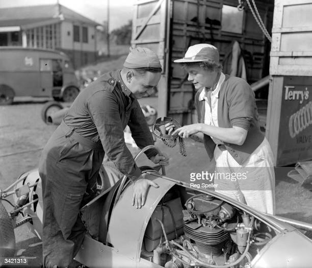 Chief mechanic Miss D Arnott explaining a problem with the engine of an Arnott 500cc racing car to its driver Peter Taylor at Crystal Palace circuit.