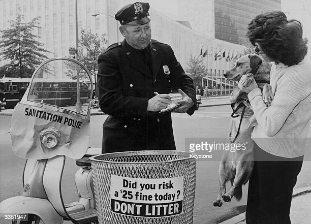 An officer of the New York sanitation police apprehending a woman whose dog has failed to take note of the don't litter signs As part of the...