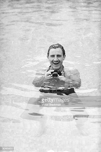 English racing driver Graham Hill using an underwater camera in a swimming pool at Monaco before the grand prix