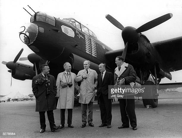 Members of the original Dam Busters crew stand in front of a Lancaster bomber like the ones they flew during the Second World War