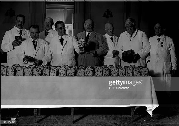 Judges, of the national currant cake championship, examining some of the final ninety entries at the Connaught Rooms, London.