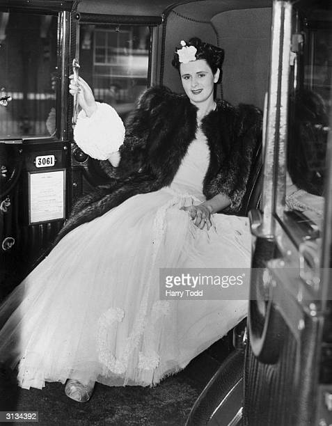 Woman in a semi-crinoline, made fashionable by Queen Elizabeth II, which can be worn in a taxi without damage.