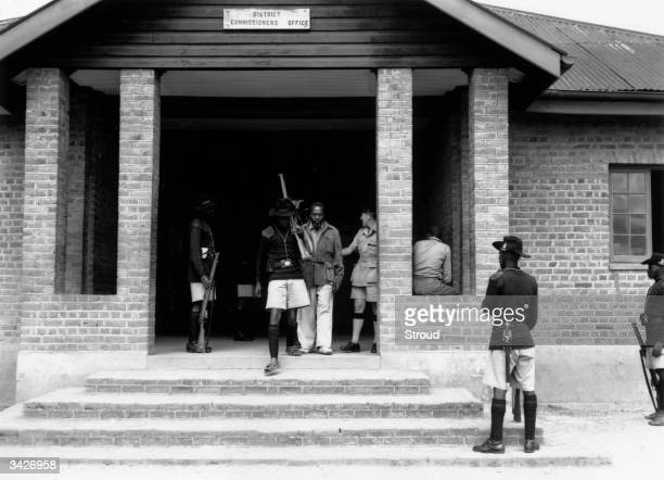 Future Kenyan president Jomo Kenyatta being led out of the District Commissioner's Office in Kenya charged with leading the Mau Mau Rebellion against...