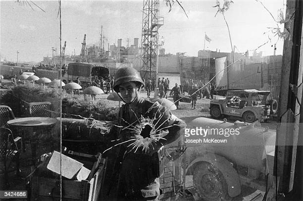 A soldier can be seen through a bullet shattered window as British and French forces unload equipment at Port Said during the Suez Crisis Original...