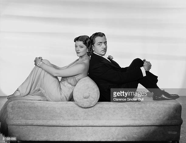 Myrna Loy as Nora Charles sits back to back with William Powell as Nick Charles in the film 'After the Thin Man' directed by W S Van Dyke