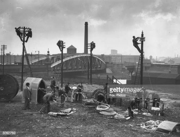 Telephone men in the making receive training in erecting telephone poles and cables at Old Trafford in Manchester