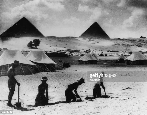 Stripped to the waist Tommies of the British forces toil in the heat of the midday sun in the shadow of the Egyptian pyramids