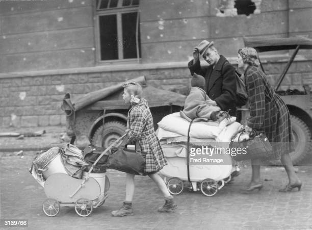 German civilian refugees who have been living in air raid shelters in wartorn Aachen in west central Germany flee from the city