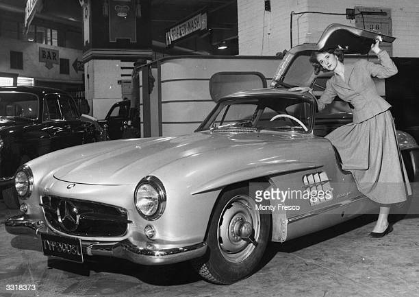 A young woman demonstrates the 'gull wing' door opening of a MercedesBenz 300SL Sports Coupe at the London International Motor Show at Earls Court