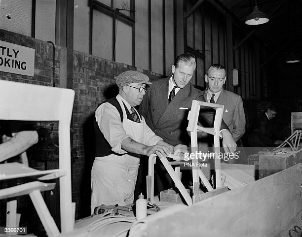 Prince Philip pays a visit to the Remploy Factory in Barking Essex and discusses the construction of laminated furniture with craftsman F T Bunyan...