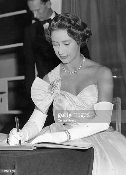 Princess Margaret signs the visitors book at the European School at Arusha in Tanganyika