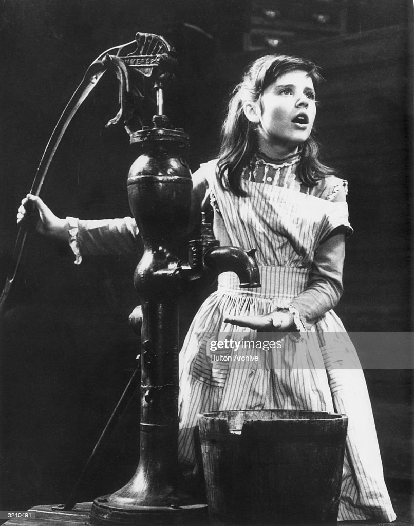 American actor Patty Duke stands at an iron water pump, portraying Helen Keller in a scene from William Gibson's play 'The Miracle Worker,' on stage at the Playhouse, New York City.