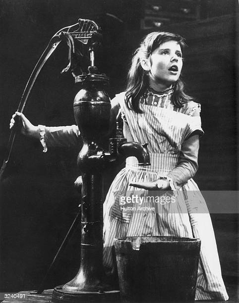 American actor Patty Duke stands at an iron water pump portraying Helen Keller in a scene from William Gibson's play 'The Miracle Worker' on stage at...