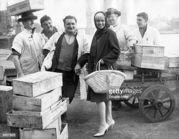 English film actress Diana Dors with a group of fish porters at Billingsgate Market London She is at Billingsgate to film scenes for the film 'The...
