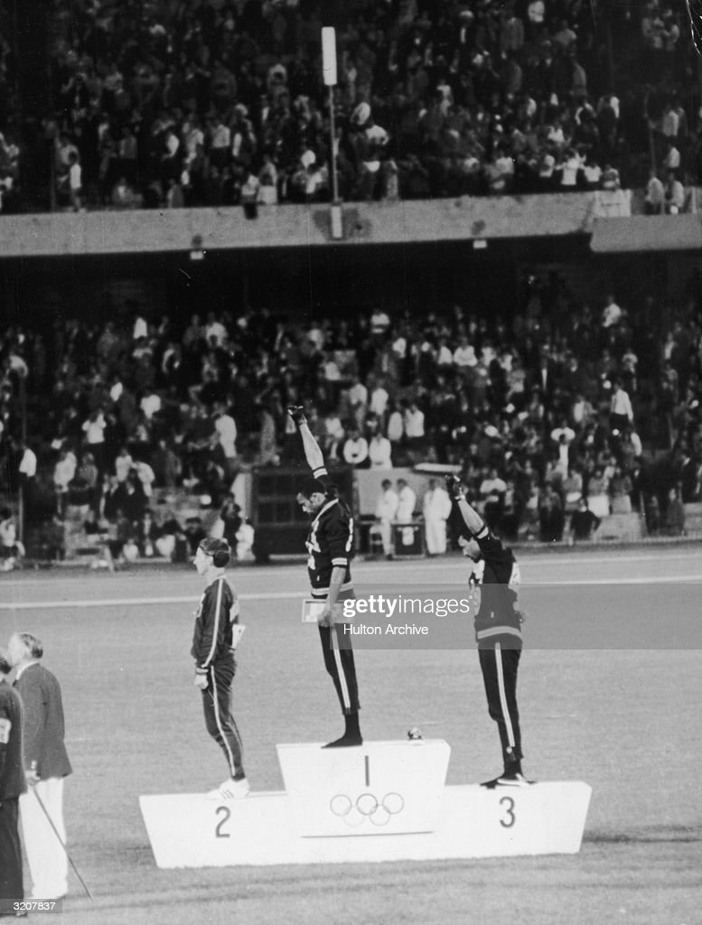 American track and field athletes Tommie Smith and John Carlos, first and third place winners in the 200 meter race, protest with the Black Power salute as they stand on the winner's podium at the Summer Olympic games, Mexico City, Mexico.