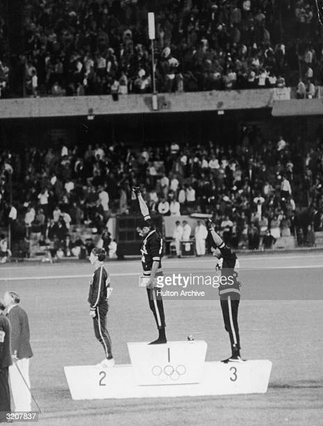 American track and field athletes Tommie Smith and John Carlos first and third place winners in the 200 meter race protest with the Black Power...