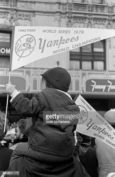 New York A young boy sits on his fathers shoulders and holds a Yankees banner at a ticker tape parade celebrating their World Series win