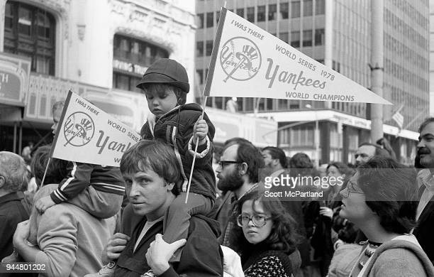 New York A young boy with a Yankees banner in hand sits on his fathers shoulder's at a ticker tape parade along Broadway's Canyon Of Heroes The...