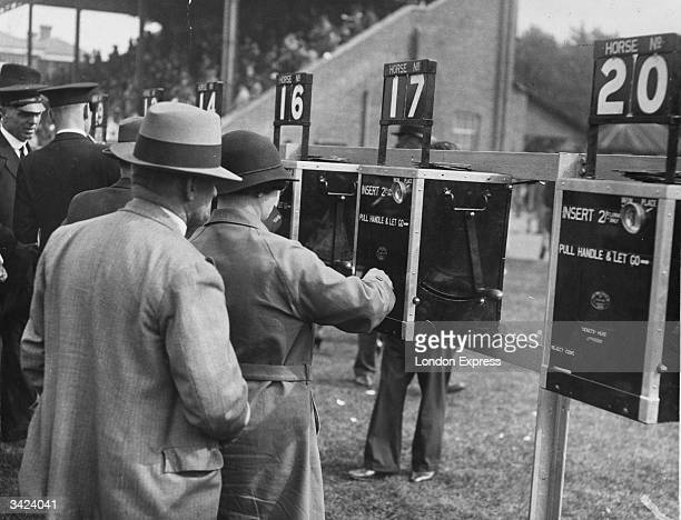Racegoers using new automatic tote machines at Windsor Races. By putting a coin in the slot and pulling a lever, each machine delivers a ticket for a...