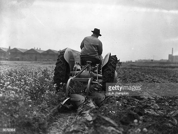 Demonstrating a new Ferguson tractor and ploughshare the latter can be raised from the driver's seat enabling the tractor to be driven along a road...
