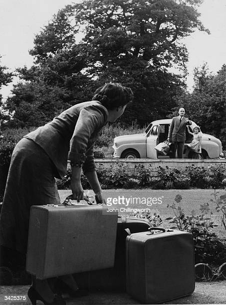 A family putting their luggage into a Standard Eight motor car made by the Standard Motor Company before a trip to the countryside Original...