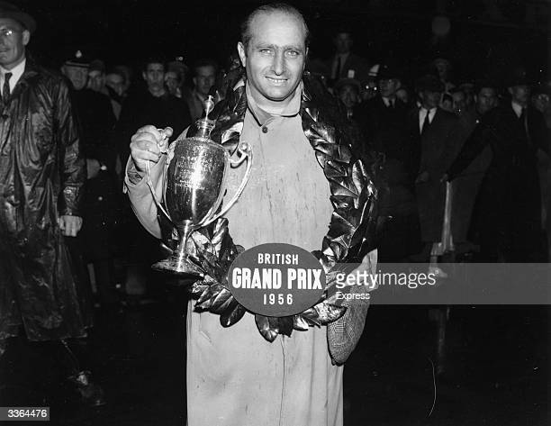 Argentinian racing driver Juan Fangio with his cup after winning the British Grand Prix at Silverstone